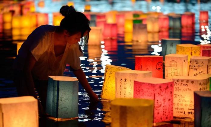 Uma mulher coloca lanternas de papel acesas em memória das vítimas do bombardeio atômico de 1945 em Hiroshima, no rio Motoyasu em frente ao Domo Bomba Atômica no Parque Memorial da Paz em Hiroshima TORU YAMANAKA / AFP