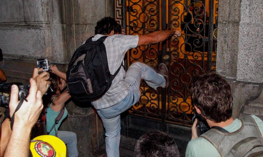 Manifestante força a grade do prédio da Alerj Foto: Pedro Kirilos / Agência O Globo