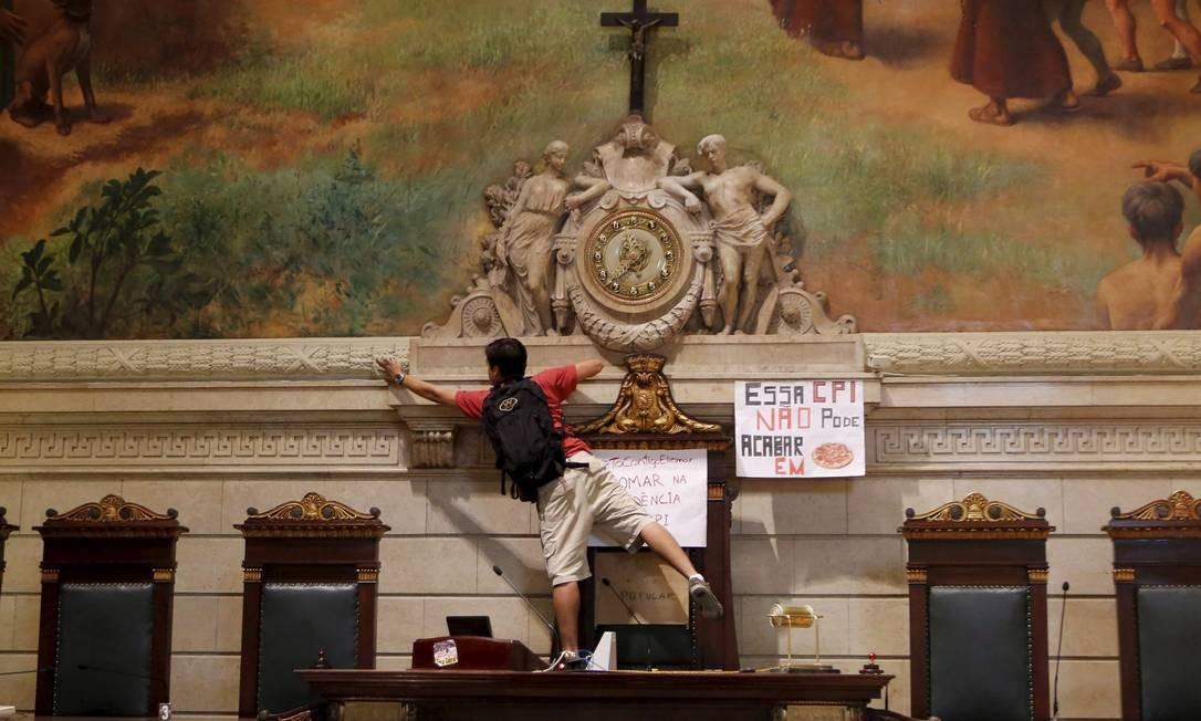 De pé na mesa da presidência da Câmara, manifestante fixa cartazes contra a composição da CPI dos Ônibus Hudson Pontes / O Globo