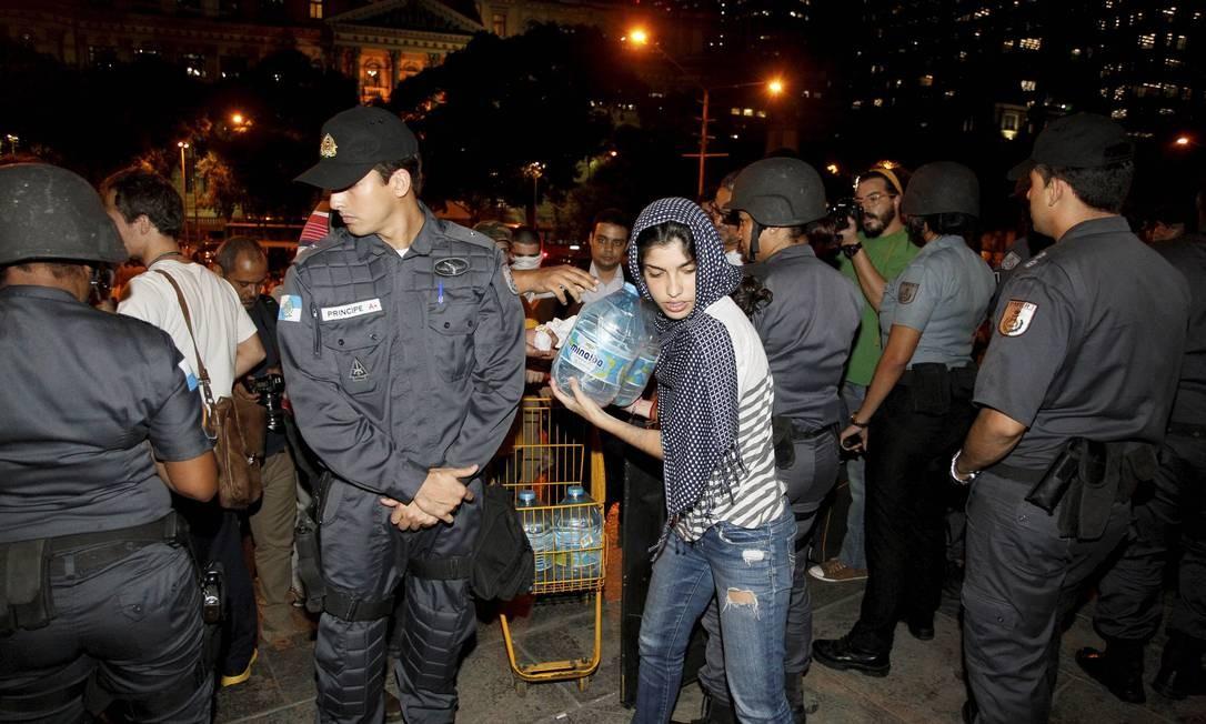 Mulher distribui água para os manifestantes Domingos Peixoto / Agência O Globo