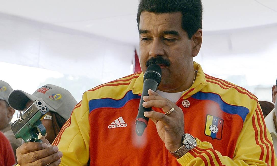 Nicolás Maduro observa uma arma enquanto discursa durante um evento para promover um programa de desarmamento público Foto: JUAN BARRETO / AFP