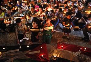 Palestinos acedem velas e fazem orações em memória dos islamistas mortos no Egito Foto: Adel Hana / AP