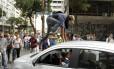 Manifestante sobe em um carro preso em meio ao engarrafamento na Avenida Rio Branco -
