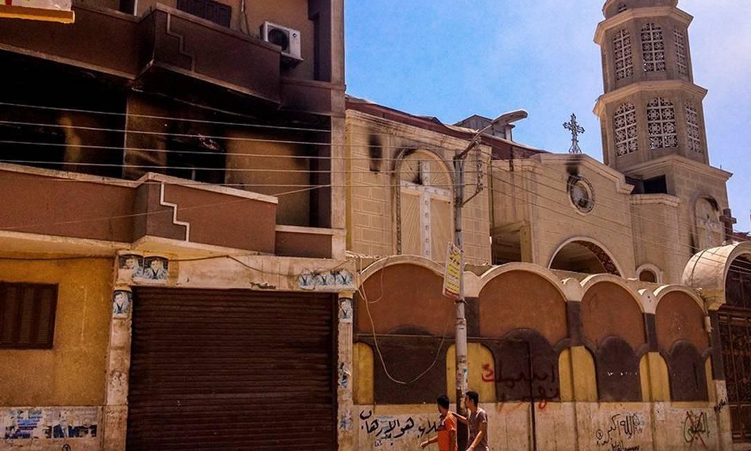 Dois egípcios passam por uma igreja católica parcialmente queimada em Minya Foto: - / AFP