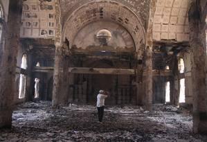 Marcas do sectarismo. Homem fotografa o que sobrou de igreja copta incendiada por extremistas pró-Irmandade Muçulmana na cidade de Minya Foto: AP/15-8-2013