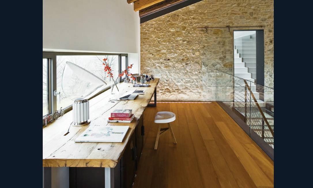 Um mezanino, com uma ampla janela, pode ser muito bem aproveitado como local de trabalho, com uma simples e ampla mesa feita com madeira de demolição Foto: Reprodução da internet
