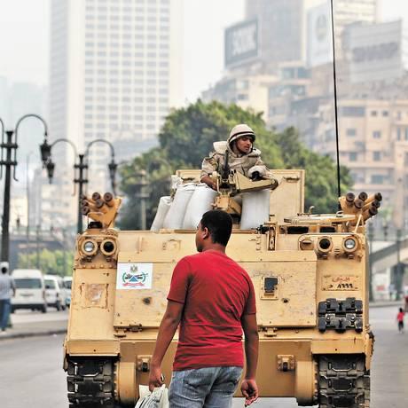 Vida que segue. Egípcio passa por veículo blindado que protege a Praça Tahrir: população se diz cansada de rotina de protestos pós-Mursi Foto: AP/16-8-2013