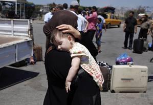 Uma mulher palestina carrega sua filha enquanto deixa o cruzamento de Rafah entre o Egito e o sul da Faixa de Gaza, após seu fechamento devido à recente violência na Península do Sinai Foto: IBRAHEEM ABU MUSTAFA / REUTERS