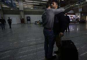 Glenn Greenwald (à esq.) abraça o companheiro David Miranda (à dir.) no aeroporto Tom Jobim nesta segunda-feira Foto: RICARDO MORAES / REUTERS