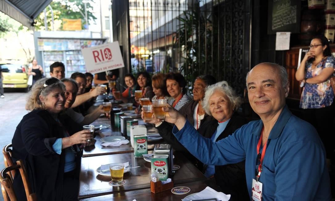 Grupo brinda durante visita na Adega Potugália enquanto degusta bolinhos de bacalhau Adriana Lorete/O Globo