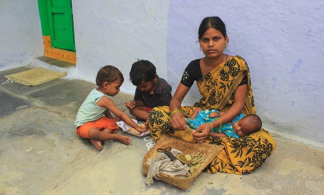Ghazala*, de 17 anos, enrola cigarros de tabaco enquanto cuida dos três filhos em Kadiri, Índia Foto: Davinder Kumar/ Plan Asia