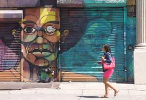 Jovem caminha por uma rua comercial do Harlem Foto: Eduardo Maia / O Globo