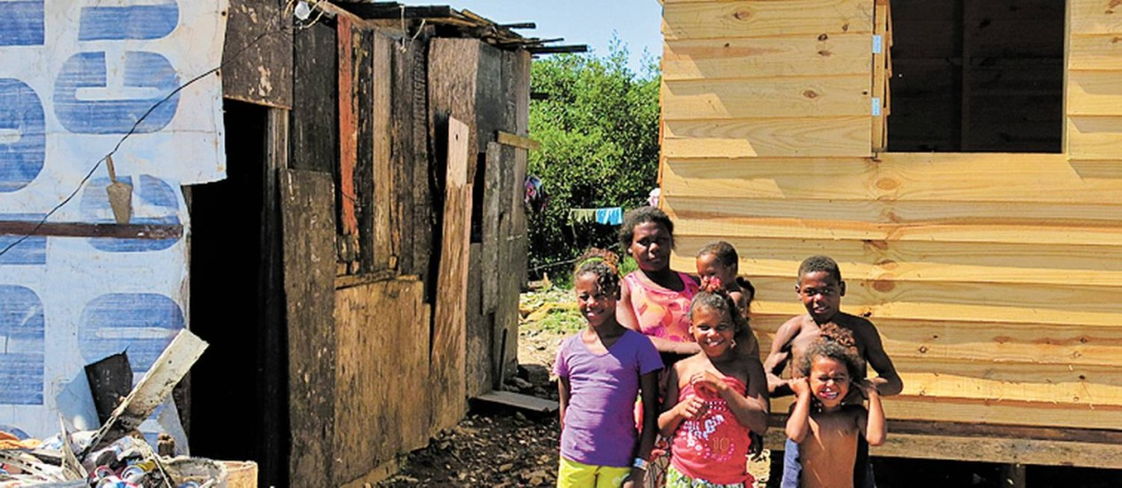 Mara com os filhos: contraste entre a casa nova (à direita) e a velha Foto: Maria Elisa Alves / O Globo