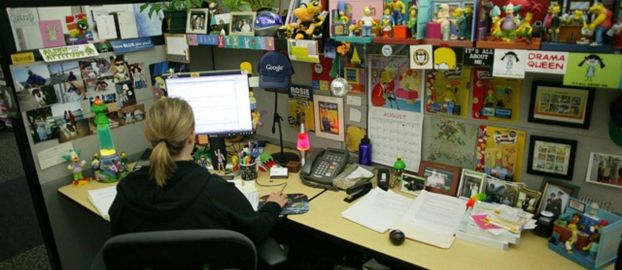 Mesa de funcionária do Google é repleta de objetos, bonecos da série 'Os Simpsons', post-its e fotos espalhadas, numa 'bagunça' organizada Foto: Divulgação