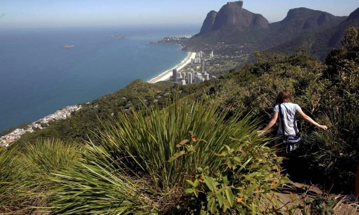 Turista desce a trilha, em direção à favela Custódio Coimbra / Agência O Globo