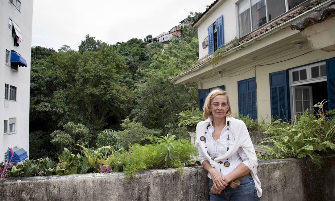 """Emily Pirmez, diretora do filme """"Vendo ou alugo"""", na sacada do dúplex onde vive, com algumas casas de comunidades vizinhas ao fundo Foto: Simone Marinho/Agência O Globo"""