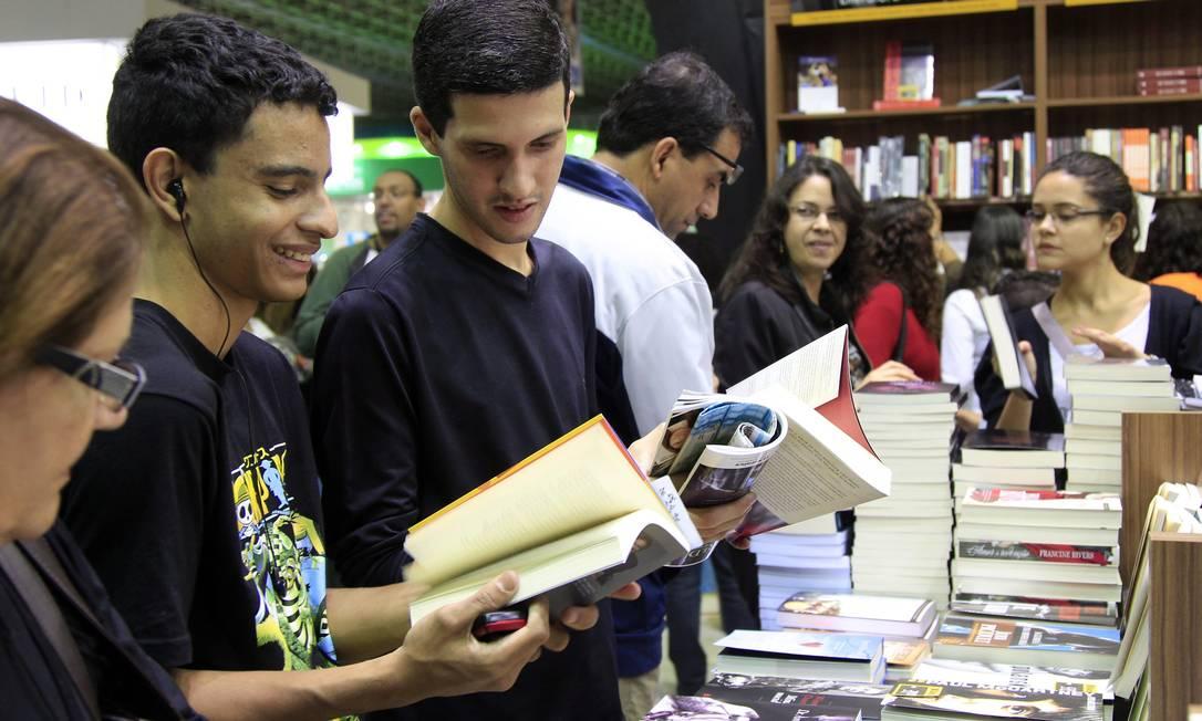 Jovens folheiam livros em estande da 15ª Bienal do Livro, em setembro de 2011 Foto: Mônica Imbuzeiro / Agência O Globo