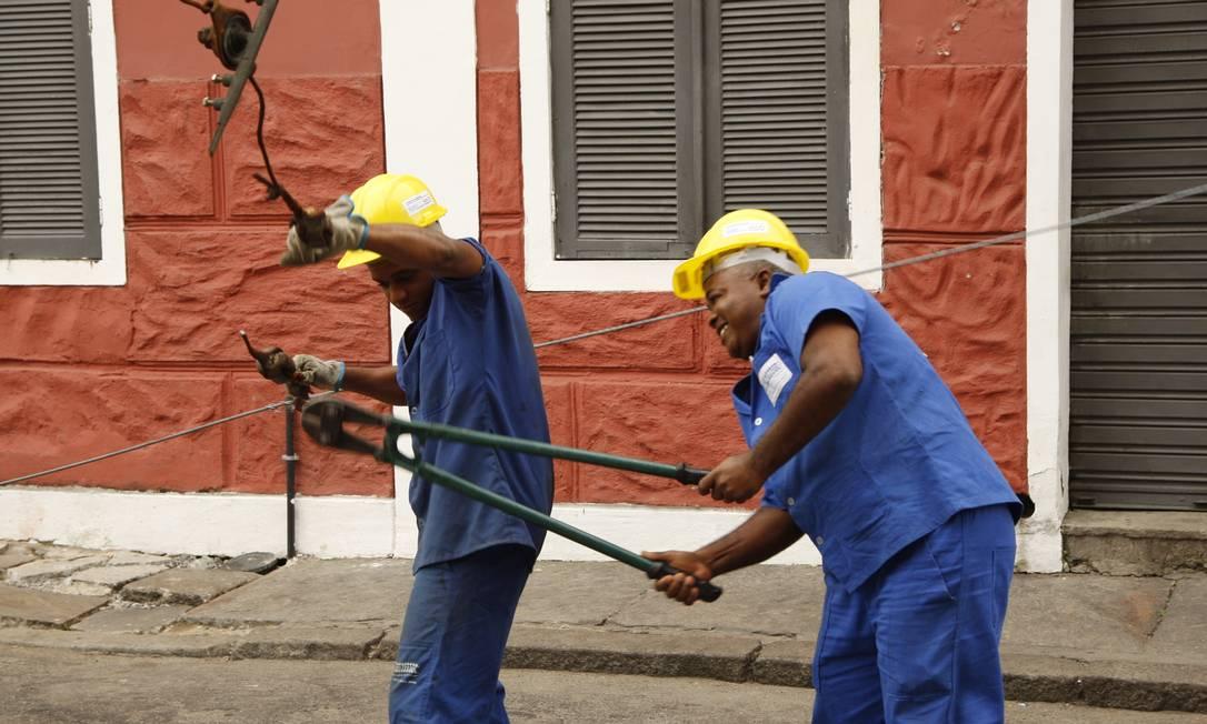 Técnicos retiram os cabos da antiga rede aérea no Largo dos Guimarães Foto: Marcos Tristão / Agência O Globo