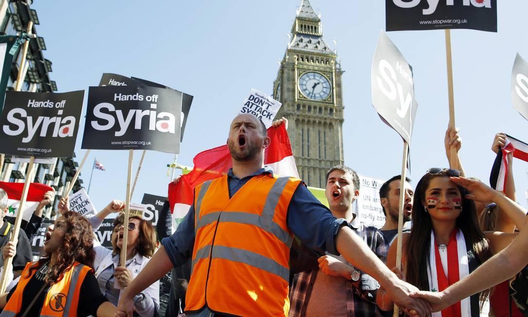 Manifestantes seguram cartazes durante protesto contra a intervenção militar na Síria no centro de Londres . Legisladores britânicos rejeitaram a proposta do primeiro-ministro David Cameron para o envolvimento britânico em ataques militares destinadas a punir o regime sírio pelo uso de armas químicas Foto: OLIVIA HARRIS / REUTERS