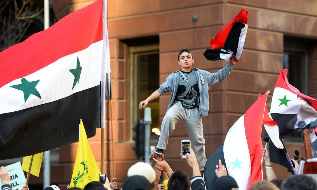 Um menino com a bandeira da Síria participa do protesto em Sydney Foto: WILLIAM WEST / AFP