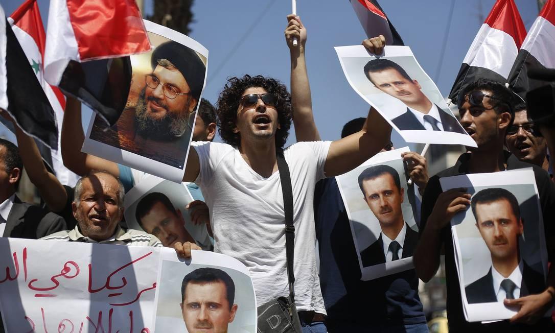 Manifestantes palestinos com fotos do presidente da Síria, Bashar al-Assad e líder do Hezbollah, Sayyed Hassan Nasrallah durante uma manifestação contra possíveis ataques do governo sírio, no City Bank de Ramallah Foto: MOHAMAD TOROKMAN / Reuters
