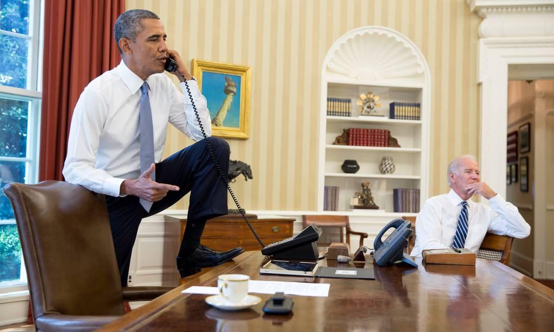 O presidente Barack Obama conversa ao telefone no Salão Oval, na Casa Branca com presidente da Câmara dos Representantes, o republicano John Boehner, de Ohio, enquanto é observado pelo vice-presidente Joe Biden. Obama vai pedir ao Congresso que autorize ação militar contra o governo da Síria. Foto: Pete SOUZA / AFP / The White House