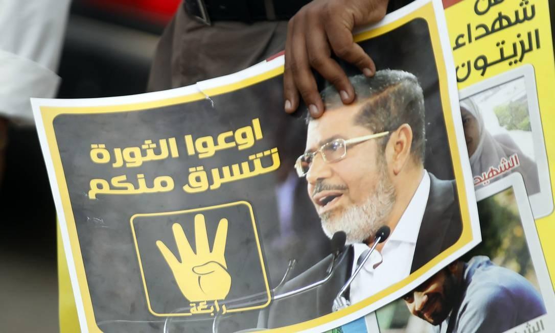 """Membro da Irmandade Muçulmana e seguidor do presidente deposto Mohamed Mursi segura um cartaz chamando """"as pessoas a proteger a revolução"""" Foto: AMR ABDALLAH DALSH / REUTERS"""