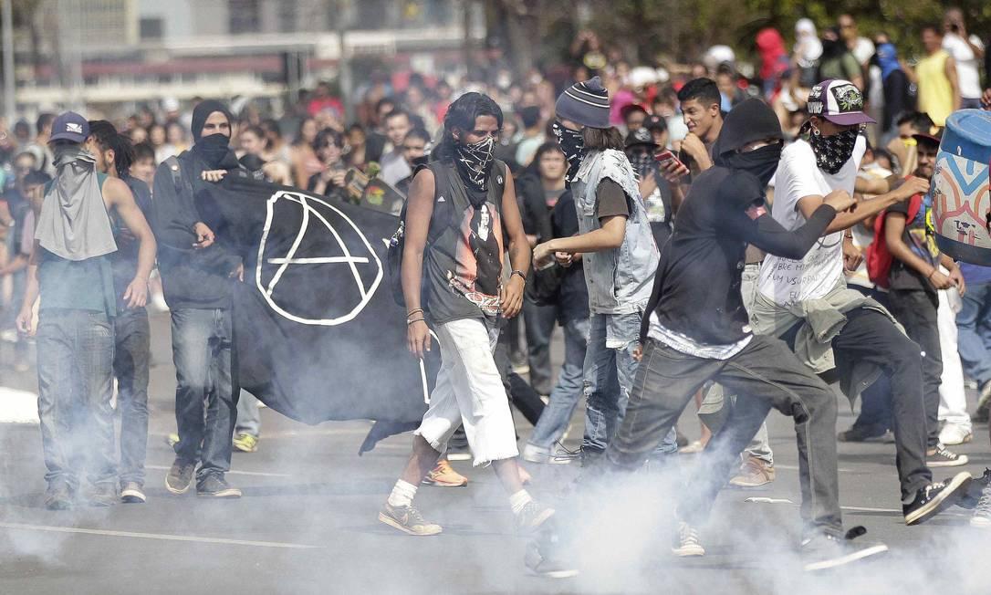 Manifestantes mascarados em meio a bombas de gás lacrimogêneo lançadas pela polícia perto do estádio Mané Guarrincha, em Brasília Foto: UESLEI MARCELINO / REUTERS