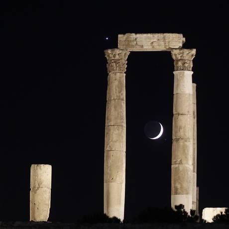 A Lua crescente e o planeta Vênus (à esquerda) são vistos no Templo de Hércules, em Amã, na Jordânia Foto: MUHAMMAD HAMED/REUTERS