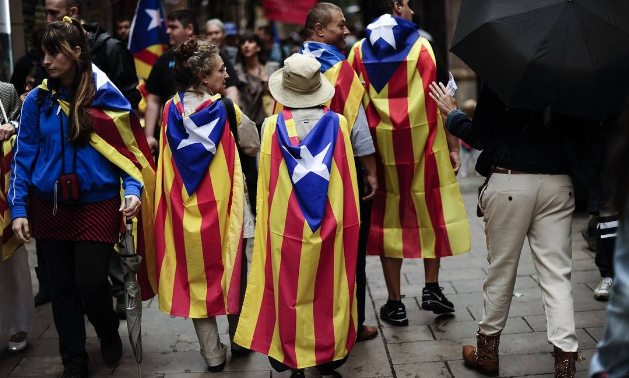 Ativistas enrolados em bandeiras da Catalunha caminham pelas ruas de Barcelona Foto: JOSEP LAGO / AFP