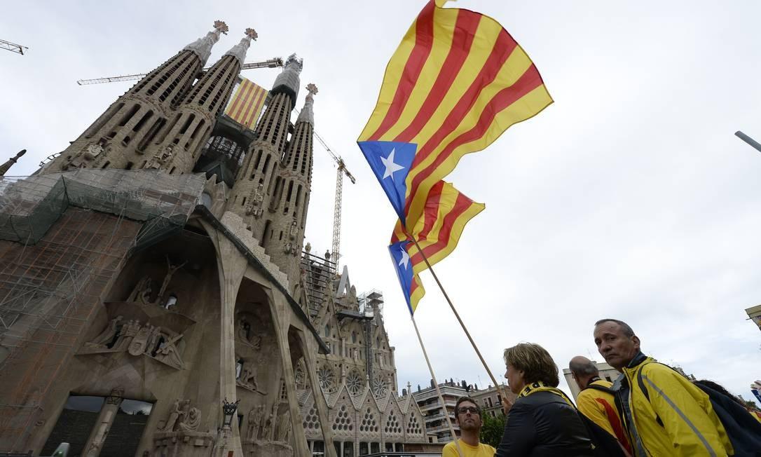 Defensores da independência da Catalunha exibem bandeiras da região em frente à sagrada Família em Barcelona Foto: LLUIS GENE / AFP