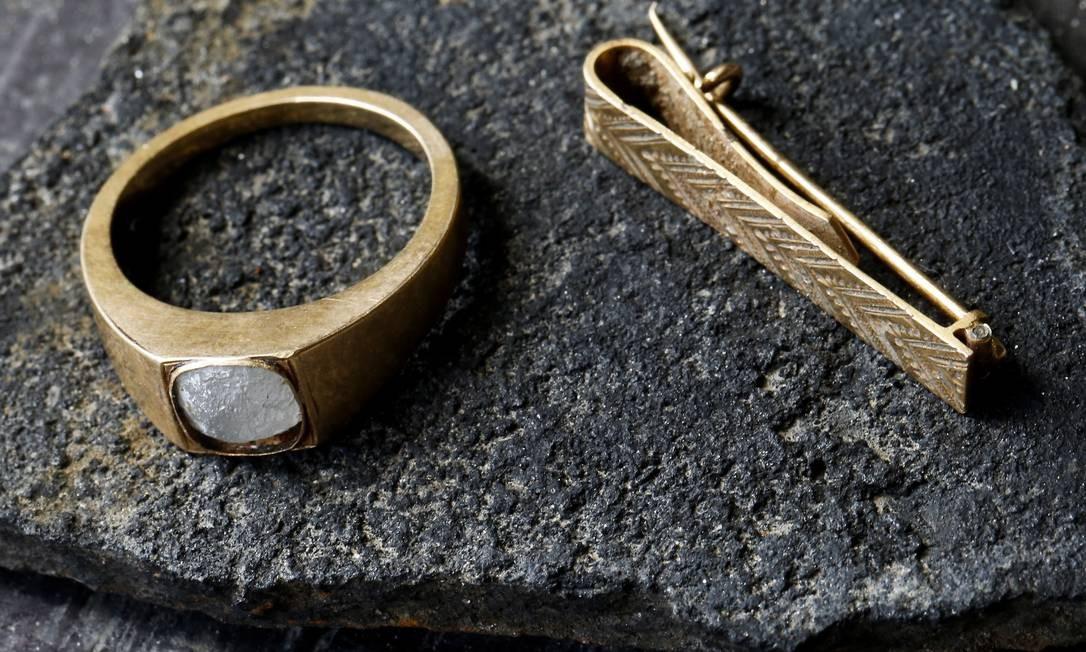 Anel e prendedor de gravata, ambos feitos de ouro, também localizados no sítio arqueológico dos fundos da antiga estação Leopoldina Foto: Guito Moreto / Agência O Globo