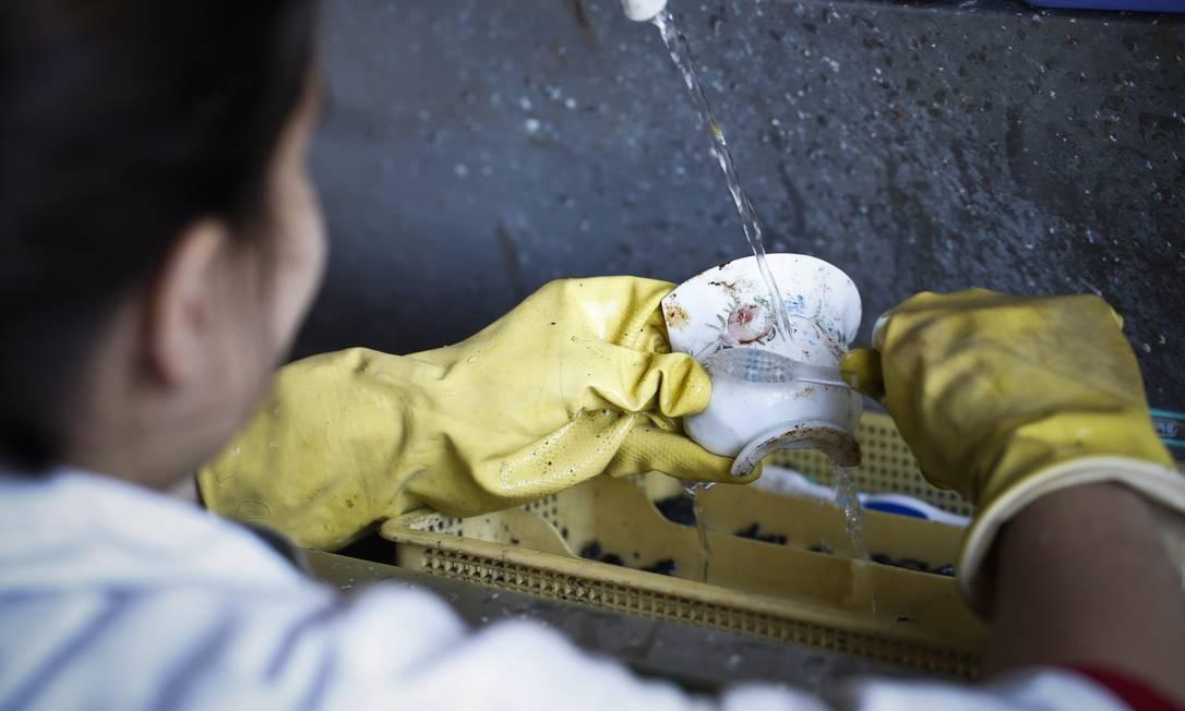 Uma integrante da equipe lava uma peça encontrada no sítio Foto: Guito Moreto / O Globo