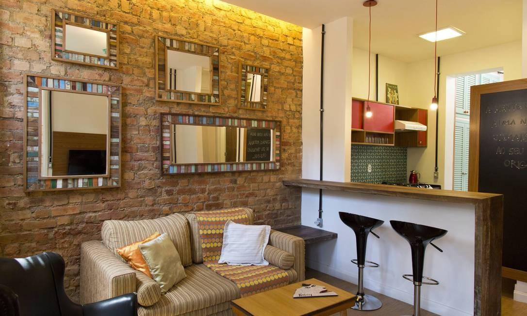 Casa transformada tem tijolos originais à mostra na decoração da sala, que foi integrada à cozinha Foto: Mônica Imbuzeiro/Agência O Globo