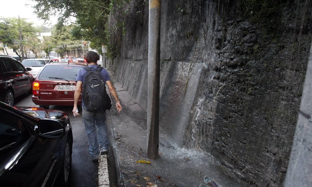 Cachoeira de esgoto. A água suja desce pelo paredão, obrigando as pessoas a andarem entre os carros Foto: Felipe Hanower / Agência O Globo