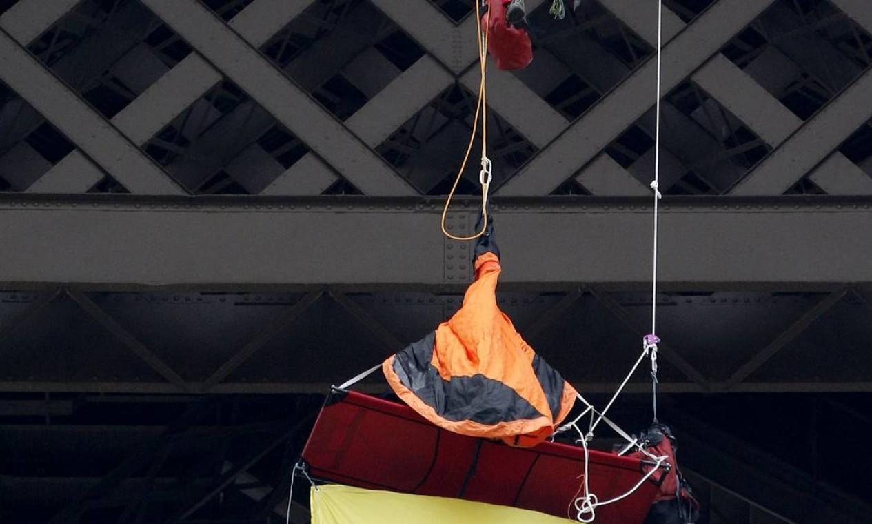 Bombeiro conversa com o ativista da Greenpeace pendurado na Torre Eiffel, em Paris, capital da França Foto: Christophe Ena / AP
