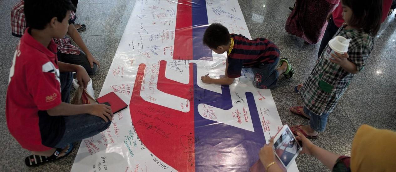 Visitantes escrevem em cartaz para homenagear passageiros desaparecidos do voo MH370 da Malaysia Airlines Foto: MOHD RASFAN / AFP