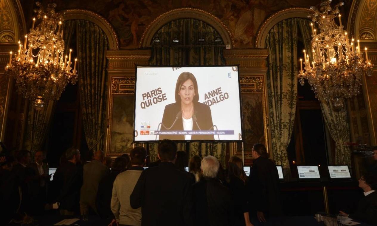 Jornalistas observam em um telão a imagem de Anne Hidalgo, eleita prefeita de Paris Foto: MIGUEL MEDINA / AFP