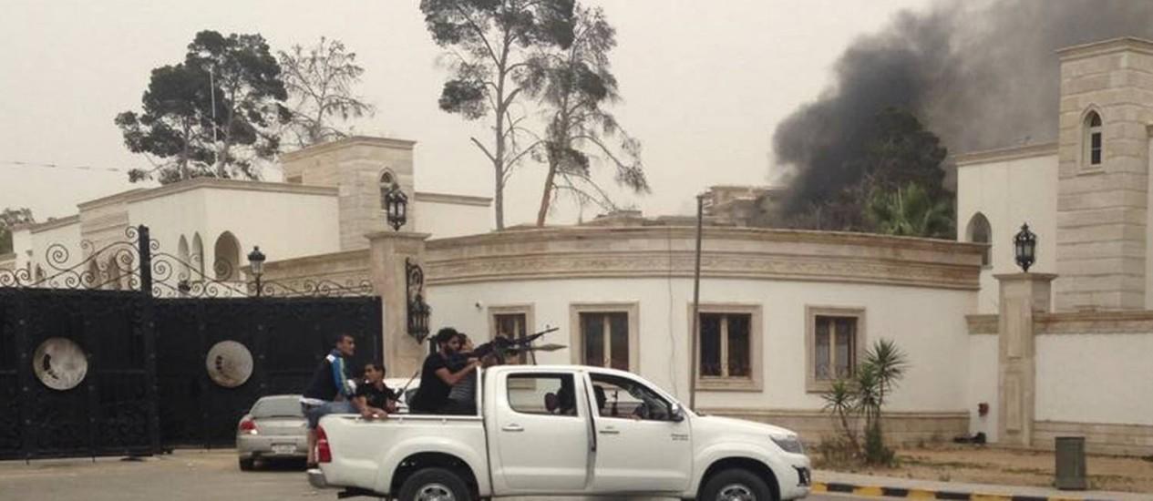 Homens armados circulam perto do Congresso da Líbia, em Trípoli, enquanto nuvem de fumaça se forma sobre o Parlamento Foto: STRINGER / REUTERS