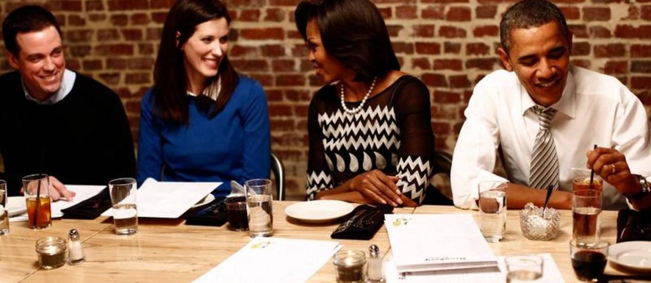 """Rotina. Obama e Michelle com a vencedora de um concurso """"Jante com os Obama"""" em 2012, no Boundary Road, um dos points na noite de Washington Foto: LUKE SHARRETT / AFP"""