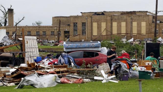 Uma mulher checa o telefone em seu quintal, rodeada de destroços na cidade de Van, no Texas Foto: Mike Stone / Reuters