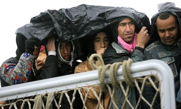 Imigrantes se protegem da chuva enquanto aguardam o desembarque em Porto Empedocle, na Sicília, em 17 de fevereiro Foto: Marcello Paternostro / AFP
