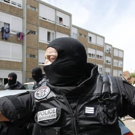 Membro das forças especiais da França guia moradora nas proximidades do local do ataque Foto: EMMANUEL FOUDROT / REUTERS