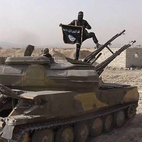 Combatente do Estado Islâmico posa em tanque do governo sírio capturado após combates em Qaryatain Foto: Uncredited/AP