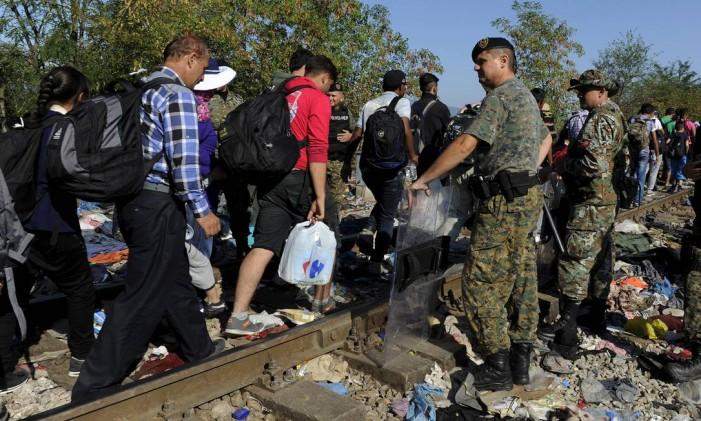 Migrantes caminham ao longo de ferrovia passando em frente às forças policiais da Macedônia prestes a cruzar a fronteira da Grécia com o país, próximo à vila de Idomeni, no domingo, 23 de agosto de 2015 Foto: ALEXANDROS AVRAMIDIS / REUTERS