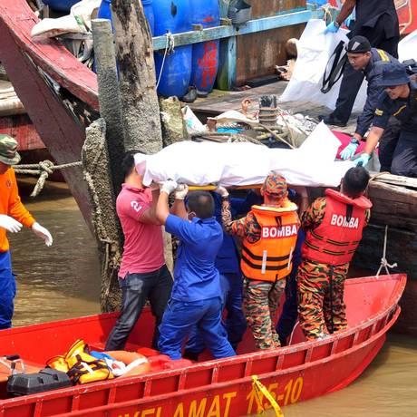 Equipes de resgate carregam um corpo de migrante que estava em naufrágio Foto: S. RAVALE / REUTERS