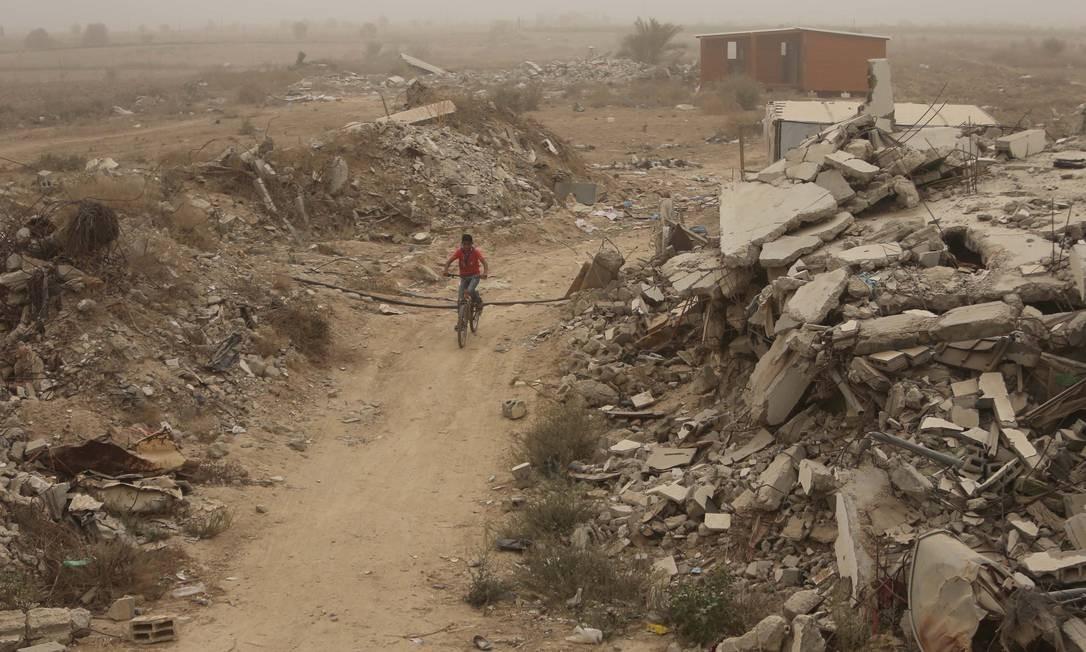 Garoto palestino pedala entre ruínas de casas na Faixa de Gaza Foto: IBRAHEEM ABU MUSTAFA / REUTERS