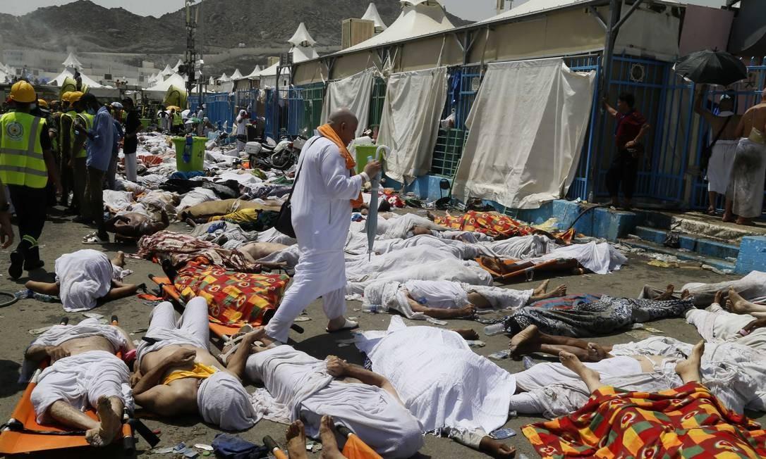 Um muçulmano caminha entre corpos da tragédia que deixou centenas de mortos na peregrinação anual a Meca Foto: Uncredited / AP
