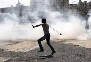 Palestino arremessa pedra contra soldados israelenses em Ramallah Foto: Abbas Momani / AFP