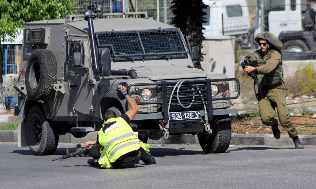 Ao se dar conta do ataque, outro militar israelense se aproxima para detê-lo Foto: STRINGER / REUTERS